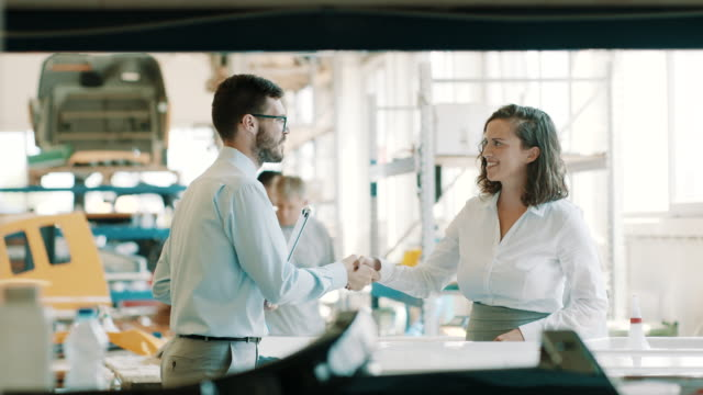 business colleagues shaking hands in factory - coworker stock videos & royalty-free footage
