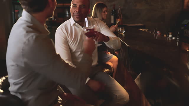 business colleagues talking while toasting with wine in a bar. - colleague stock videos & royalty-free footage