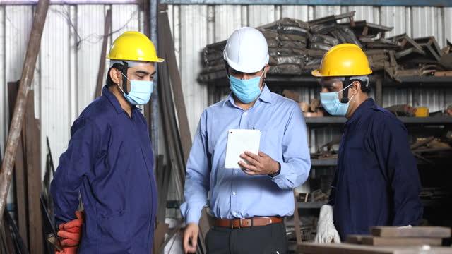 工場でデジタルタブレットを使用するビジネスの同僚 - 土木技師点の映像素材/bロール