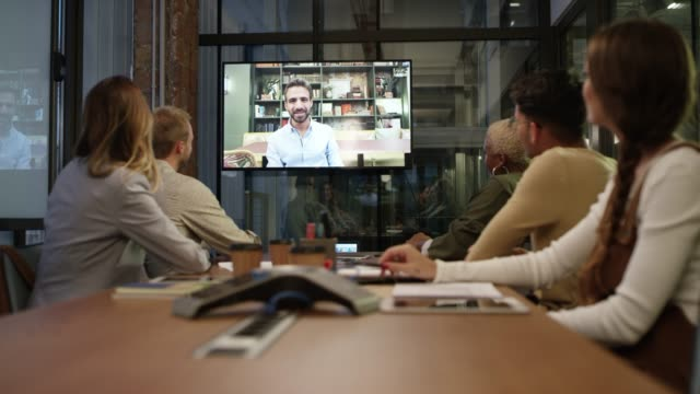vídeos de stock e filmes b-roll de business colleagues video conferencing at office - interatividade