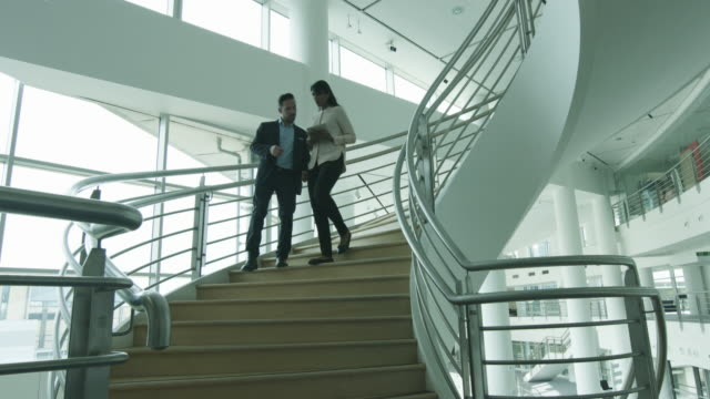Business colleagues walking down spiral staircase
