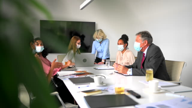 business colleagues wearing protective masks during meeting in time of covid-19 - conference table stock videos & royalty-free footage