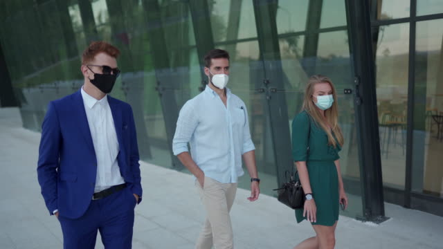 business colleagues with protective face masks, taking a break from work, walking and talking in front of office building - three people stock videos & royalty-free footage