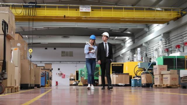stockvideo's en b-roll-footage met bedrijfscollega's die met tabletcomputer in fabriek werken - buiten de vs