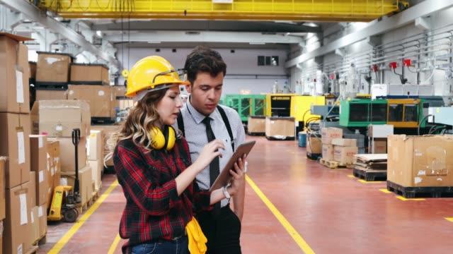 工場でタブレット pc を使用するビジネスの同僚 - 倉庫作業員点の映像素材/bロール