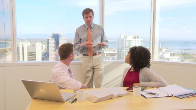 business collegues discussing work in office - dreiviertelansicht stock-videos und b-roll-filmmaterial