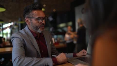 affärskonsult på ett möte på cafeteria - rea bildbanksvideor och videomaterial från bakom kulisserna