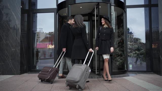 coppia d'affari che arriva in hotel e saluta un amico all'ingresso - arrivo video stock e b–roll