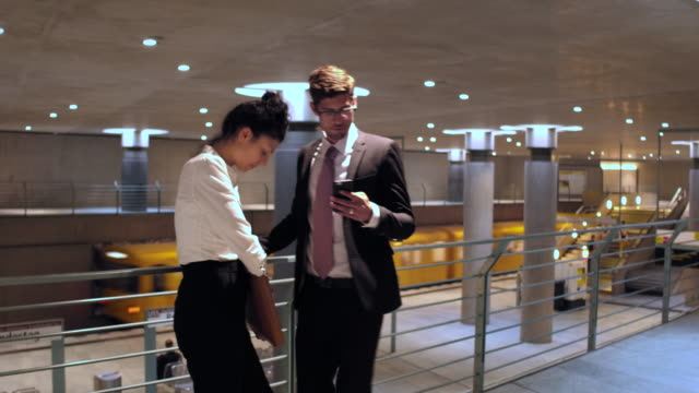 Business couple checks their phones in subway station