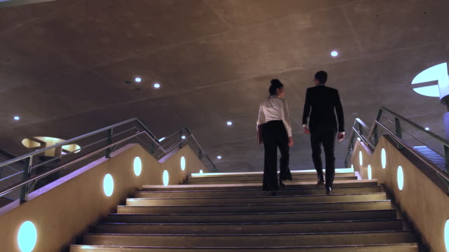 Business couple climbing stairs