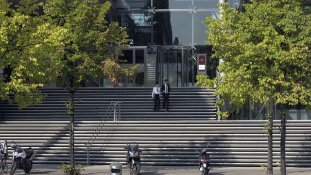 business couple coming down wide steps of office building - steps and staircases stock videos & royalty-free footage