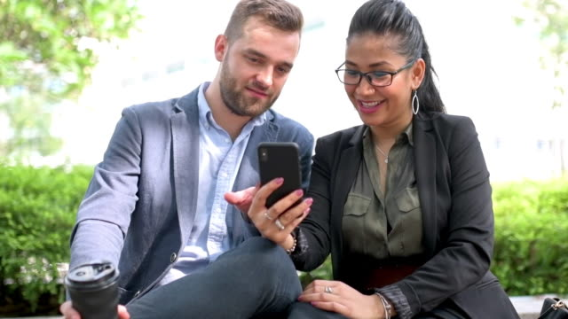 business couple discussing over smart phone - three quarter length stock videos & royalty-free footage