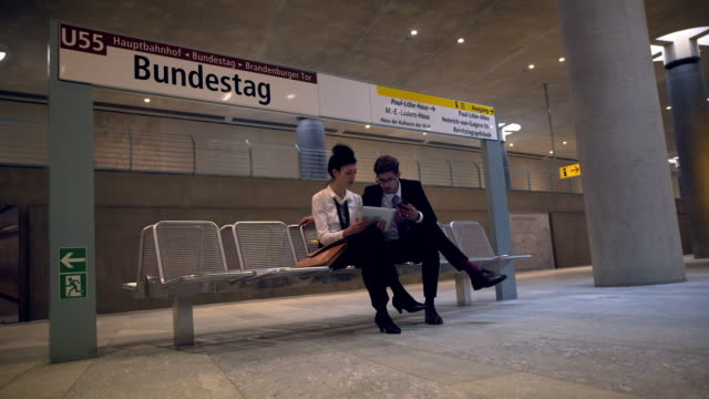 business couple discussing papers in the subway - 全套西裝 個影片檔及 b 捲影像