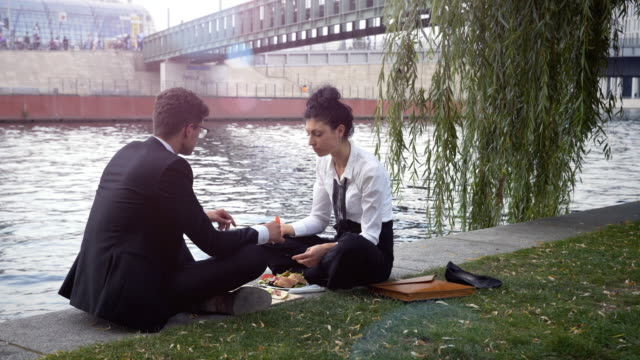 Business couple having lunch at a canal