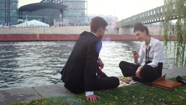 business couple having lunch at a canal - wolkenloser himmel stock-videos und b-roll-filmmaterial