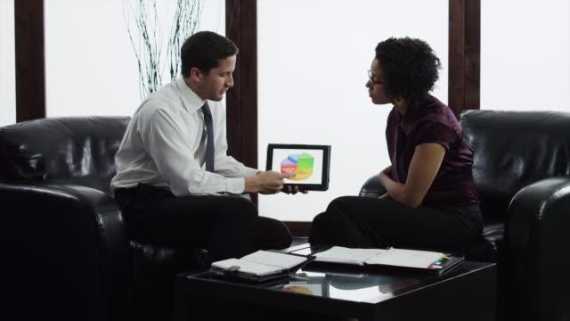 MS Business couple having meeting in lobby using digital tablet/ Orem, Utah, USA