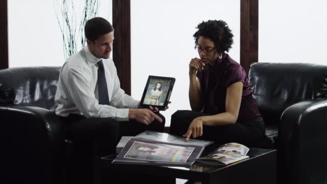 stockvideo's en b-roll-footage met ms business couple having meeting in lobby using digital tablet/ orem, utah, usa - overhemd en stropdas