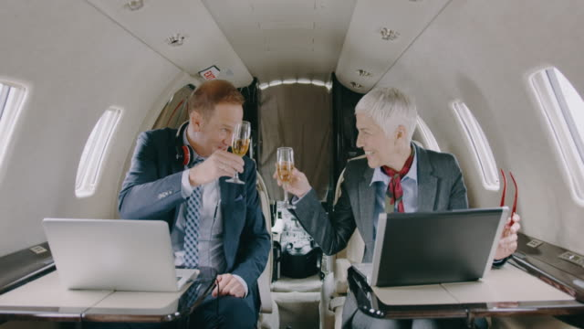 business couple in private jet airplane - business travel stock videos & royalty-free footage
