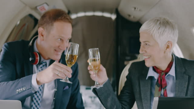 business couple in private jet airplane - wine glass stock videos & royalty-free footage