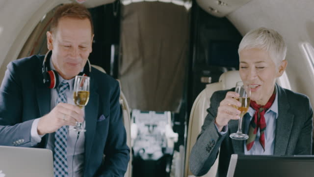 business couple in private jet airplane - vehicle interior stock videos and b-roll footage