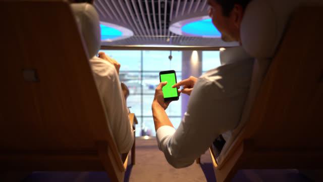 vídeos y material grabado en eventos de stock de pareja de negocios relajándose en el salón vip del aeropuerto mirando un teléfono inteligente - chroma key - sala de embarque del aeropuerto