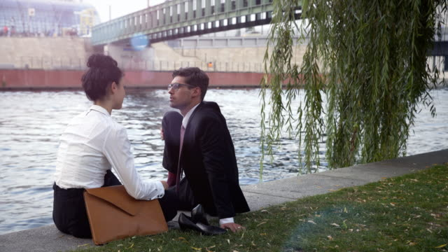 Business couple rests next to the water