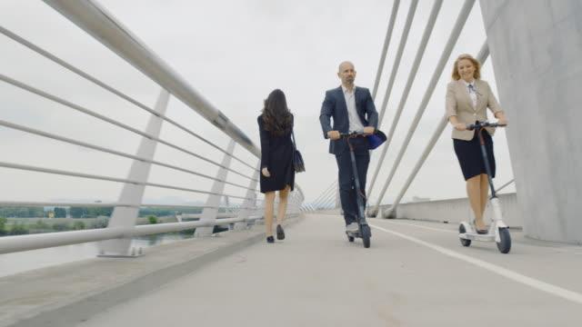 stockvideo's en b-roll-footage met slo mo business paar rijden elektrische scooters aan het werk - mid volwassen mannen