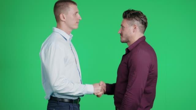 Geschäft-Paar schüttelt Hände zusammen auf grünem Hintergrund