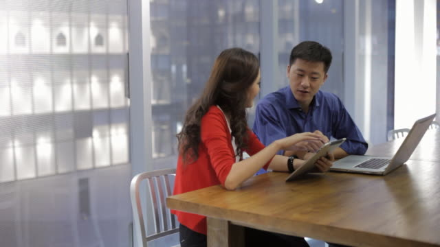MS Business couple using digital tablet and laptop in modern office / China