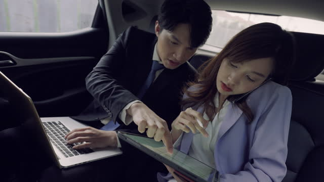 business couple using electronic organizer while travelling in car - electronic organizer stock videos & royalty-free footage