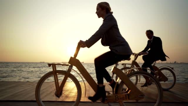 vídeos y material grabado en eventos de stock de compañeros de trabajo en bicicleta a la obra - vista de costado