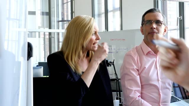 vidéos et rushes de collaborateurs d'entreprises discuter au bureau créatif - stylo