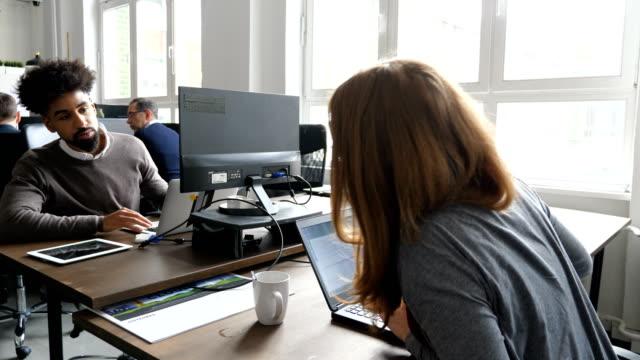 unternehmen mitarbeiter sprechen bei der verwendung von notebooks - computeranlage stock-videos und b-roll-filmmaterial
