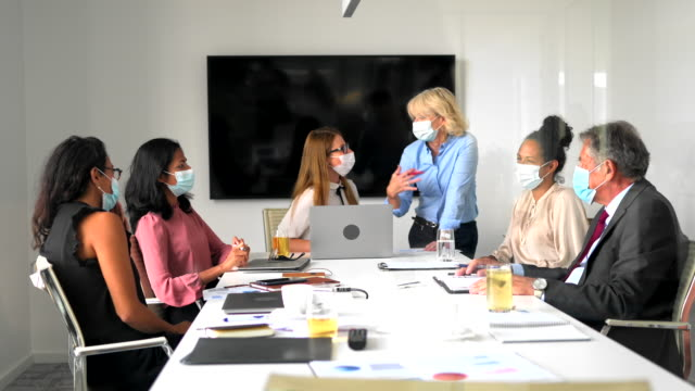 business coworkers wearing surgical masks in time of covid-19 - diversity stock videos & royalty-free footage