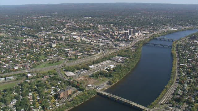 AERIAL Business district by river cutting through city / Springfield, Massachusetts, United States