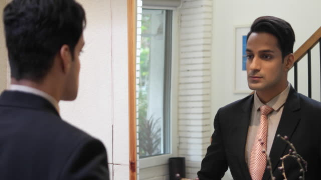 a business does last checks in the mirror before existing his house for office - 建物入口点の映像素材/bロール
