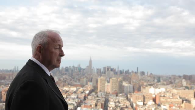 business executive on rooftop overlooking manhattan  - pensionati lavoratori video stock e b–roll