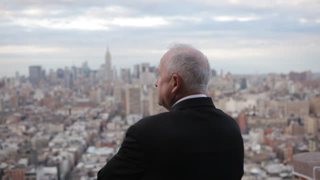 business executive on rooftop overlooking Manhattan