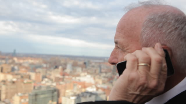 business executive talking on mobile phone on rooftop overlooking manhattan  - 薄毛点の映像素材/bロール