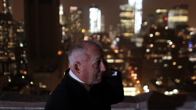business executive talking on mobile phone on rooftop overlooking manhattan  - remote location phone stock videos & royalty-free footage