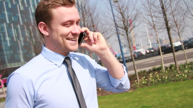 Business executive walking on phone outside of office in park