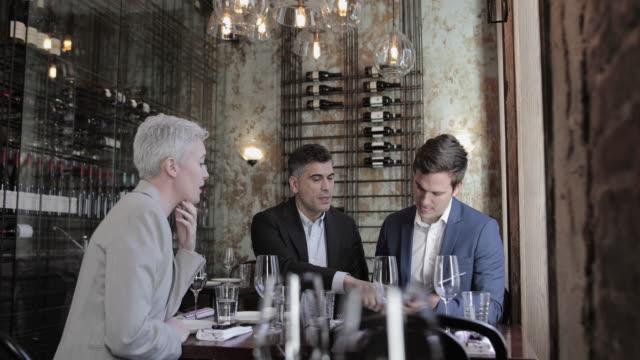 vídeos y material grabado en eventos de stock de business executives having a working lunch in a restaurant - comida del mediodía