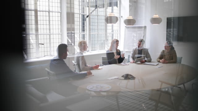 stockvideo's en b-roll-footage met business executives in a meeting - wide shot