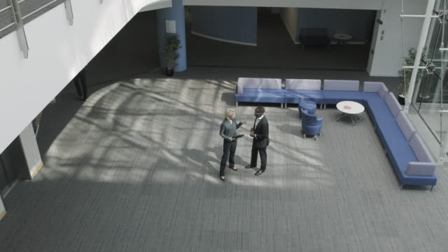 business executives walking in office lobby for meeting using digital tablet wireless technology - 建物入口点の映像素材/bロール