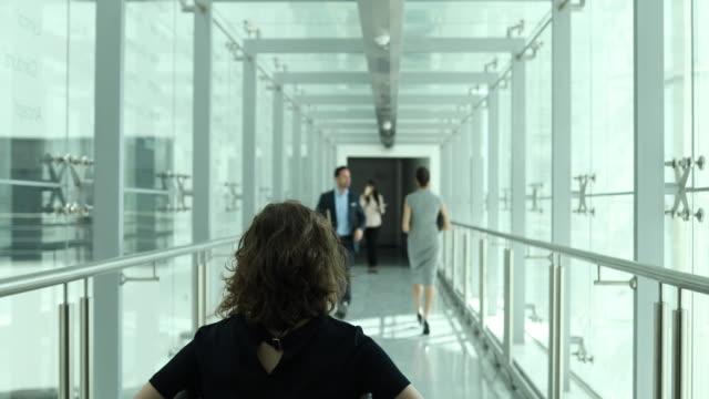 Business executives walking through busy office corridor