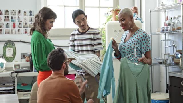 vídeos de stock e filmes b-roll de business fashion designers discussing over clothing - indústria têxtil