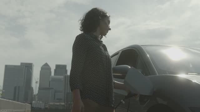 vídeos y material grabado en eventos de stock de business female charging electric car at charging station in city - coche eléctrico coche alternativo
