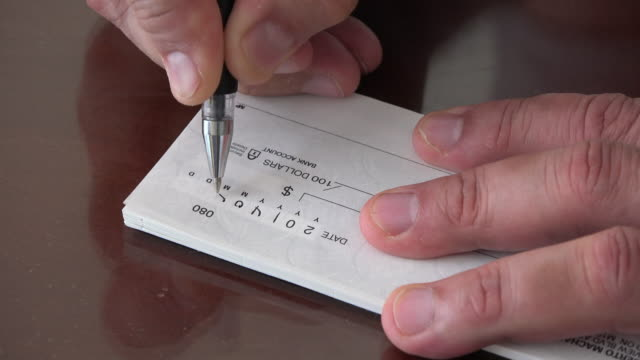 vídeos de stock, filmes e b-roll de business financial concept: man writing a cheque - financial bill