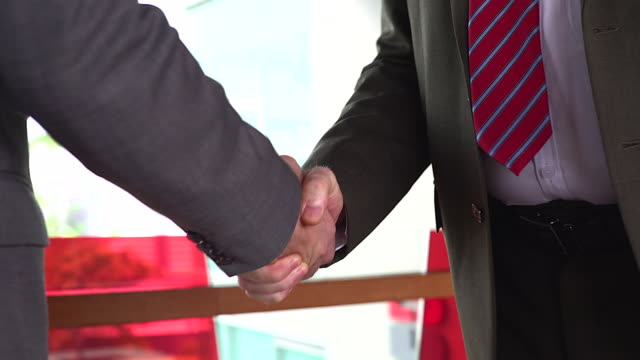 business handshake of two men demonstrating their agreement to sign agreement or contract between their firms / companies / enterprises. - contract stock videos & royalty-free footage