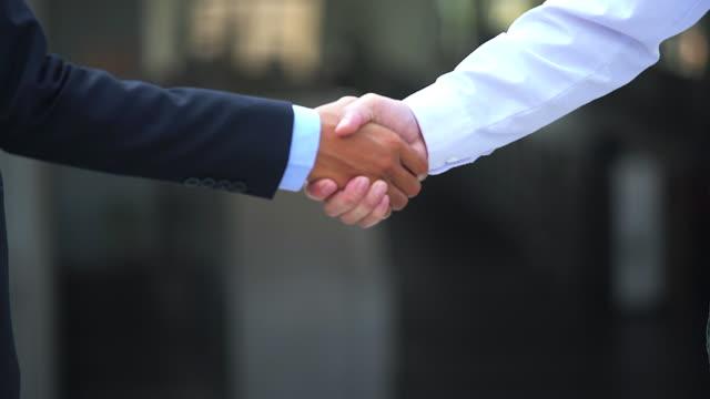 vídeos de stock, filmes e b-roll de aperto de mão de negócios de dois homens, demonstrando o seu acordo para assinar o acordo ou contrato entre suas empresas / empresas / empresas. - parceria